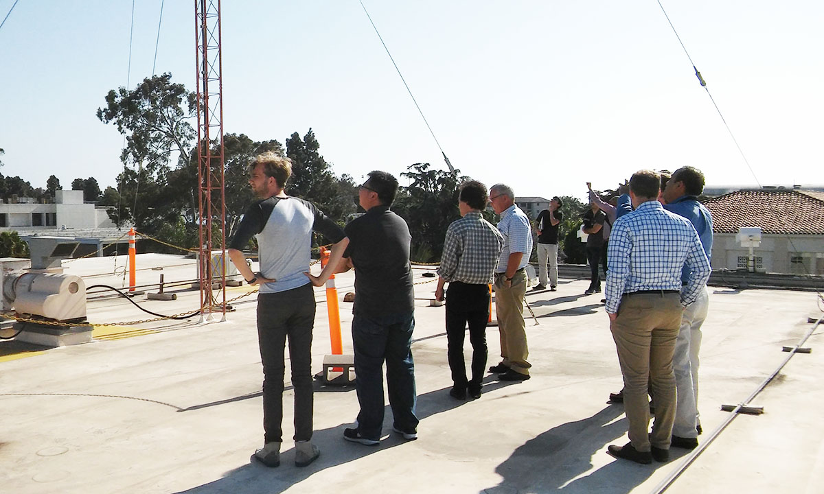 Students, faculty and industry partners on roof looking at antennae